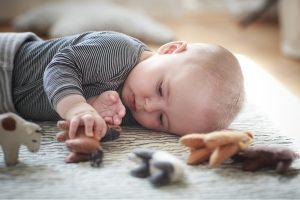 liggende baby pakt een vilten dier vast en bekijkt het