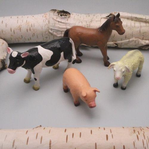 boerderijdieren tussen boomstammen op grijze achtergrond