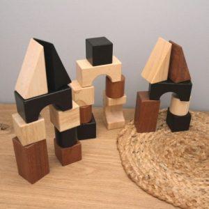 houten bouwblokken met verschillende vormen en kleuren op plank met grijze achtergrond