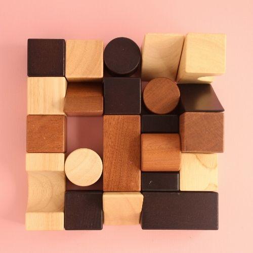 bouwblokken met verschillende vormen en kleuren in vierkant op roze achtergrond