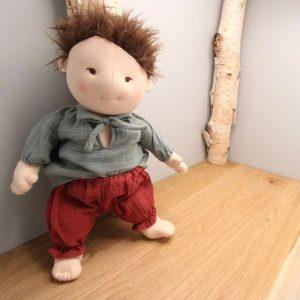 broek rood gedragen door pop victor op hout met grijze achtergrond