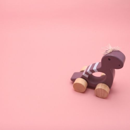 dino paars klein op wielen met roze achtergrond
