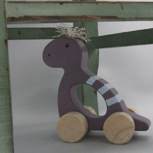 dino paars op wielen onder groene stoel