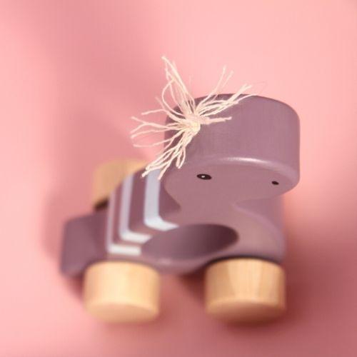 dino paars op wielen met roze achtergrond