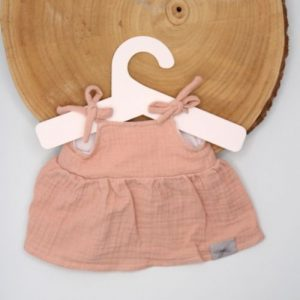 roze jurk op boomstam op grijze achtergrond