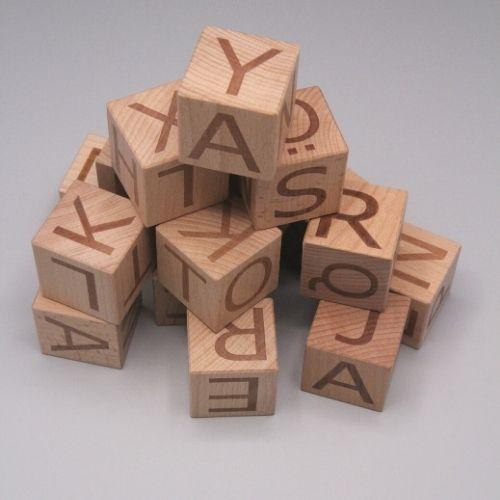 stapel letterblokken op grijze achtergrond houtenspeelgoed visionairspeelgoed