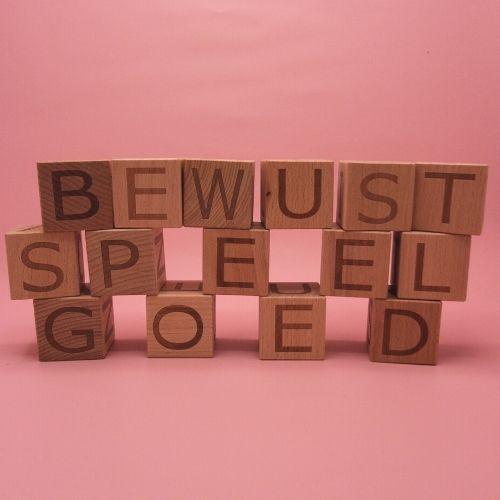 letterblokken in tekst bewust speelgoed met roze achtergrond
