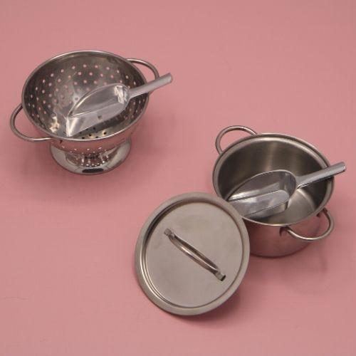 pan en vergiet met lepeltjes op roze achtergrond