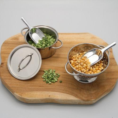 pan en vergiet met lepeltjes en garnituur op grijze achtergrond