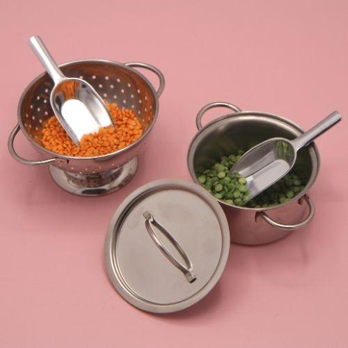 pan en vergiet met lepeltjes en vulling op roze achtergrond