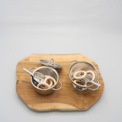 pan en vergiet met lepeltjes en ringen op grijze achtergrond