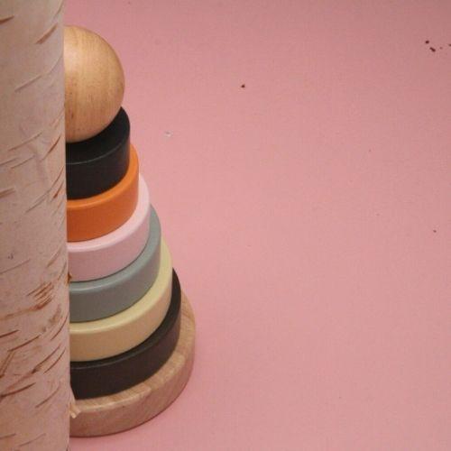 Stapeltoren ringen achter boomstam op roze achtergrond