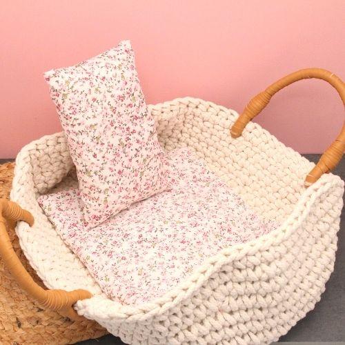 reiswieg met dekentje en kussentje op steen met roze achtergrond