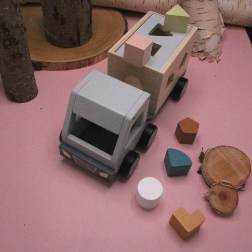 vrachtwagen met puzzelstukjes met bomen op roze achtergrond