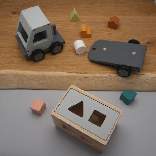 vrachtwagen met puzzelstukjes op plank met grijze achtergrond
