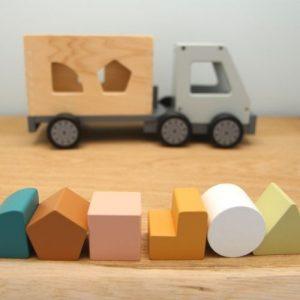 vrachtwagen van hout met puzzel blokjes op plank met grijze achtergrond
