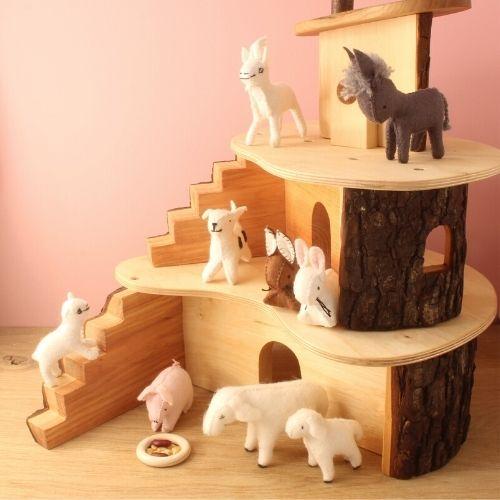 boerderijdieren van vilt in houten huis op roze achtergrond